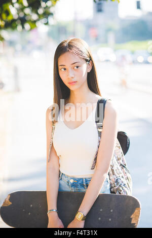 Half length of young handsome asiatic long brown straight hair woman skater holding a skateboard, posing outdoor - Stock Photo