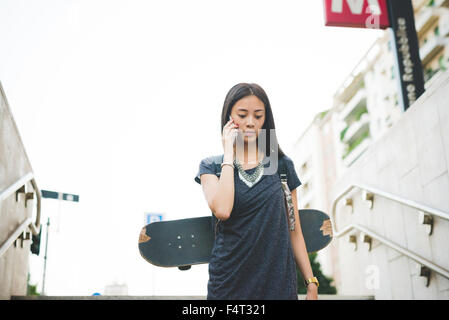 Half length of young handsome asiatic long brown straight hair woman talking smartphone, going downstairs to the - Stock Photo