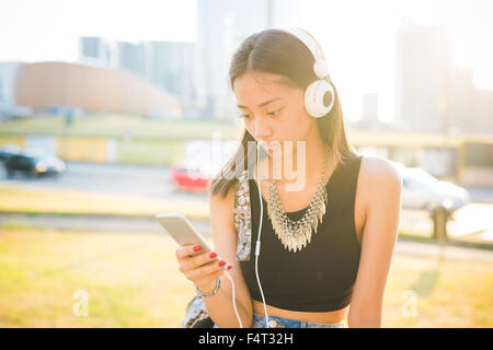 Half length of young handsome asiatic long brown straight hair woman listening music with headphone while using - Stock Photo