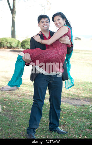 A young and happy Indian man carrying his fiance who is wearing a Sari on a sunny day in the Fall. - Stock Photo