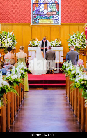 A bride and groom kneel to take their vows at a wedding - Stock Photo