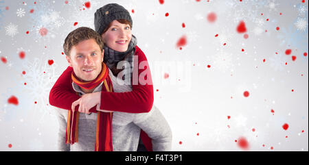 Composite image of man giving girlfriend piggy back - Stock Photo