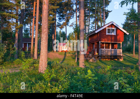 DALARNA, SWEDEN ON JULY 02, 2015. View of a timber, log cabin, lodge in the sunset. Lawn around the building. Editorial - Stock Photo