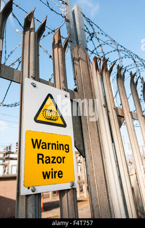 Warning sign on a fence to an electricity power substation warning of the existence of razor wire. - Stock Photo