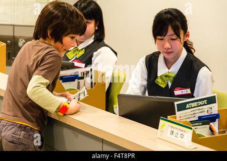 Japan, Nishinomiya, KidZania. Children's play world. Interior of bank. Western child withdrawing money over the - Stock Photo