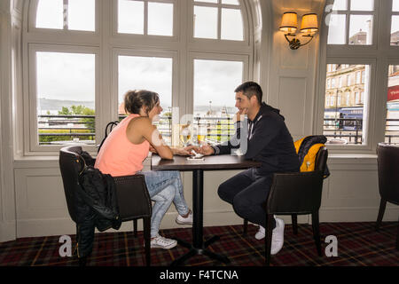 Young couple holding hands having serious relaxed conversation at pub in Argyll Hotel, Dunoon, Scotland.   ©Myrleen - Stock Photo