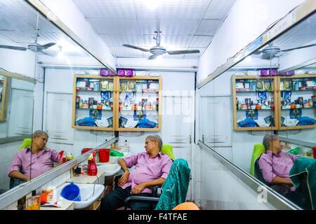 Dhaka, Bangladesh. 22nd Oct, 2015. Oct 22, 2015 - Dhaka, Bangladesh - A barbar is sleeping in his saloon at Dhaka - Stock Photo