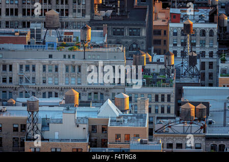 Late afternoon light over Chelsea building rooftops illuminating New York City typical water towers. Manhattan aerial - Stock Photo