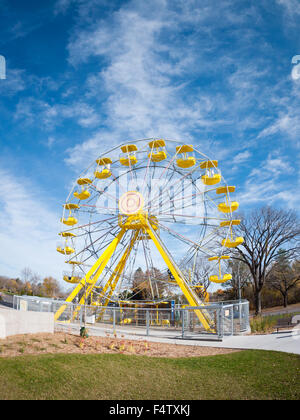 A wide angle, fisheye view of the yellow ferris wheel at the PotashCorp Playland at Kinsmen Park in Saskatoon, Canada. - Stock Photo