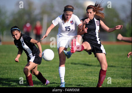 Players make contact with each other as they joust for possession of the ball during a high school soccer (football) - Stock Photo