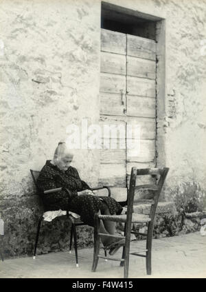 An elderly woman sitting on a chair sleeping outdoors, Italy - Stock Photo