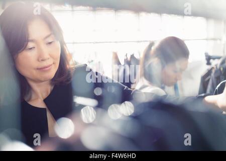 Fashion designer examining clothing on rack - Stock Photo