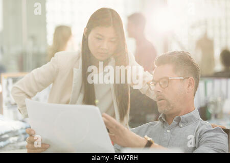 Business people discussing paperwork in office - Stock Photo
