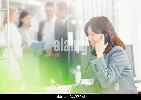 Smiling businesswoman talking on telephone in office - Stock Photo