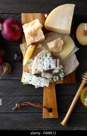 mix cheeses on cutting board, food top view - Stock Photo