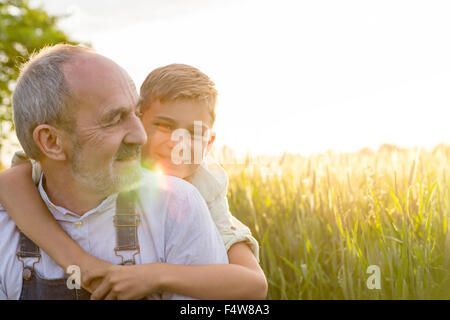 Portrait affectionate grandson hugging grandfather in rural wheat field - Stock Photo