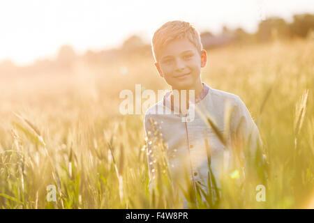Portrait smiling boy in sunny rural wheat field - Stock Photo