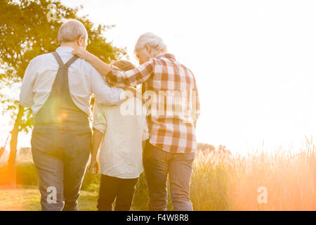 Affectionate grandparents and grandson walking along sunny rural wheat field - Stock Photo