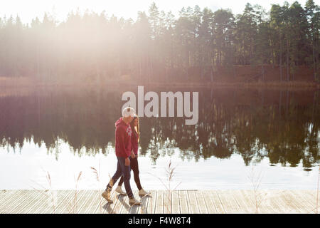 Sweden, Ostergotland, Mjolby, Couple walking on jetty at Skogssjon lake - Stock Photo