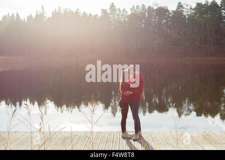 Sweden, Ostergotland, Mjolby, Couple embracing on jetty at Skogssjon lake - Stock Photo