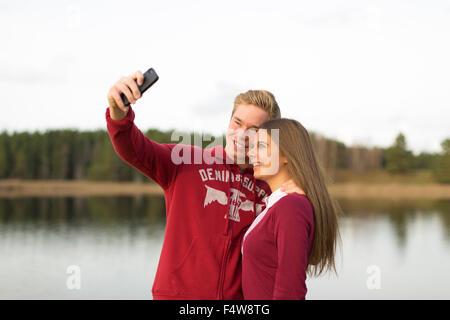 Sweden, Ostergotland, Mjolby, Couple taking selfie Skogssjon lake - Stock Photo