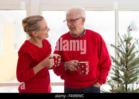 Senior couple having coffee during Christmas - Stock Photo