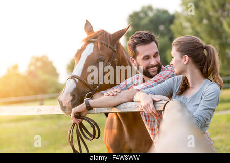 Couple with horse talking at rural pasture fence - Stock Photo