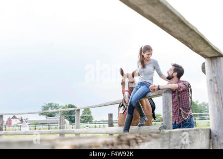 Couple and horse at rural pasture fence
