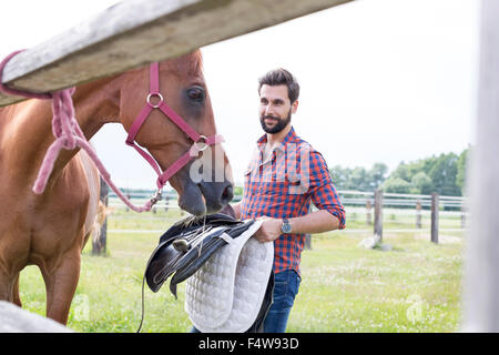 Man removing saddle from horse in rural pasture - Stock Photo
