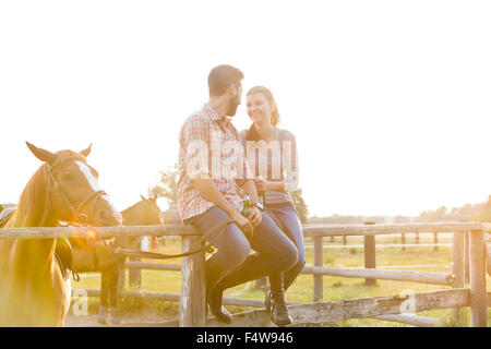 Couple with horse talking on sunny rural pasture fence