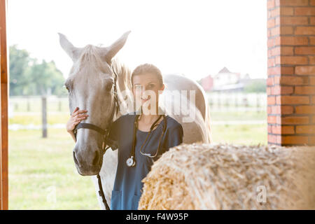 Portrait smiling veterinarian with horse in barn - Stock Photo
