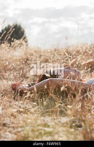 Serene woman sleeping in sunny rural field - Stock Photo