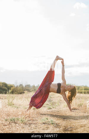 Boho woman in extended side plank yoga pose in sunny rural field - Stock Photo