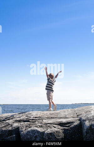 Sweden, Uppland, Runmaro, Barrskar, Boy (6-7) standing on seaside and looking at view - Stock Photo