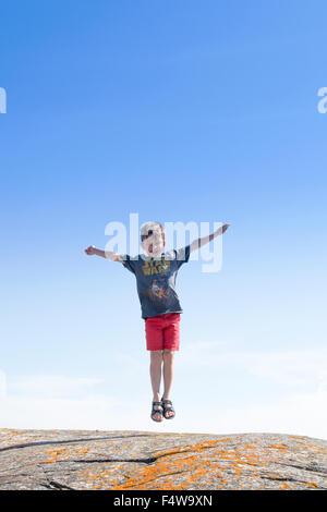 Sweden, Uppland, Runmaro, Barrskar, Boy (6-7) jumping on rock
