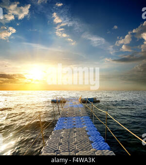 Pontoon with handrails in the sea at sunset - Stock Photo