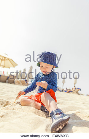 Boy (12-17 months) playing on beach - Stock Photo