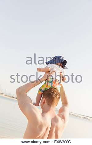 Man holding son (12-17 months) on beach - Stock Photo
