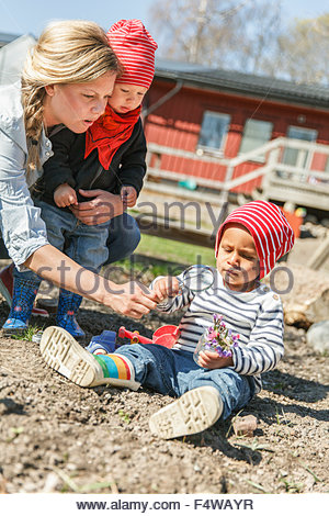 Sweden, Sodermanland, Jarna, Boys (12-17 months) playing with mother - Stock Photo