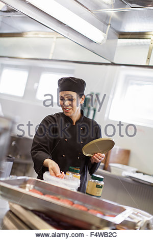 Sweden, Sodermanland, Sodertalje, Interior of industrial kitchen and people working - Stock Photo