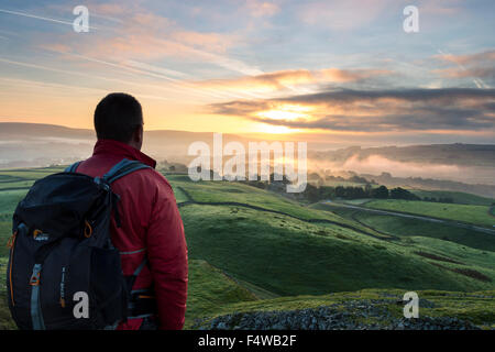 Hiker Enjoying the View Across a Misty Teesdale at Sunrise From Kirkcarrion, Lunedale, Teesdale County Durham UK - Stock Photo