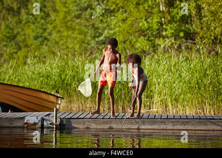 Sweden, Vastra Gotaland, Skagern, Girl (6-7) and boy (10-11) fishing in lake - Stock Photo
