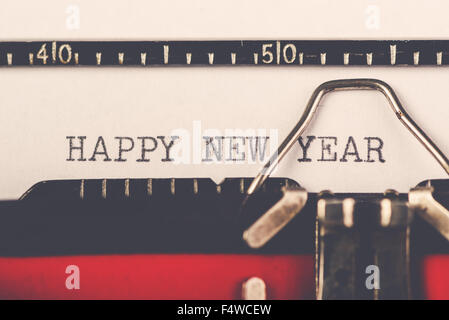 Happy New Year on old typewriter machine, hipster lifestyle holiday letter and greeting card, retro toned, selective - Stock Photo