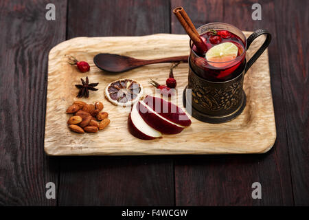Hot Toddy (mulled wine, punch) with apples and rose hips served on rustic wooden tray with almonds over dark wooden - Stock Photo