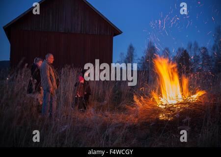 Sweden, Narke, Filipshyttan, Grandfather with grandchildren (6-7,8-9,16-17) looking at bonfire - Stock Photo