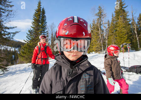 Norway, Osterdalen, Trysil, Mom and her two children (4-5, 8-9) walking down ski slope - Stock Photo