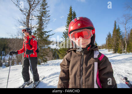 Norway, Osterdalen, Trysil, Portrait of smiling girl (4-5) standing on ski slope - Stock Photo