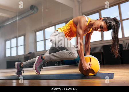 Fit female doing intense core workout in gym. Young muscular woman doing core exercise on fitness mat in health - Stock Photo