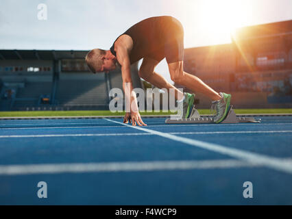 Young man on starting position ready for running. Male athlete in the starting blocks on sports track about to run. - Stock Photo