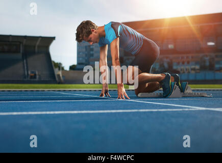 Young athlete at starting position ready to start a race. Male runner ready for sports exercise on racetrack with - Stock Photo